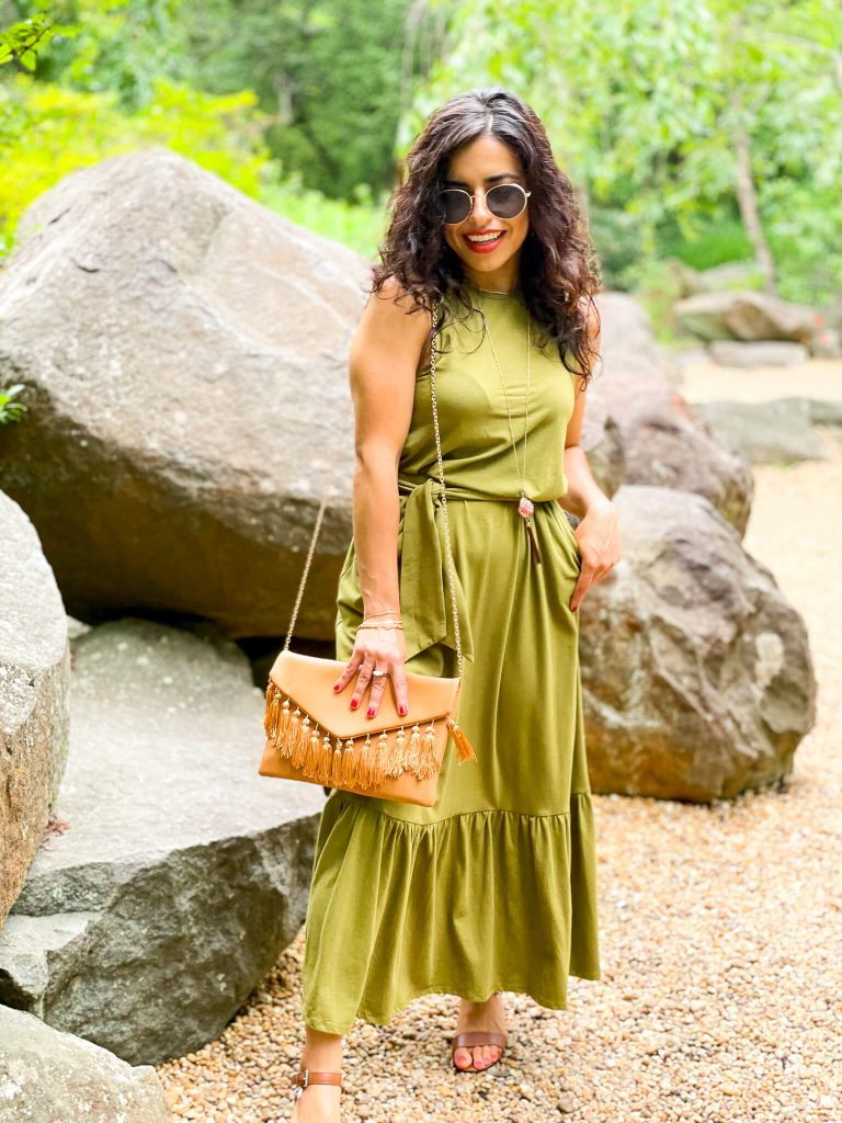 Woman wearing a green maxi dress with sandals in front of a rock formation. Carrying a tassle hand bag and wearing round sunglasses.