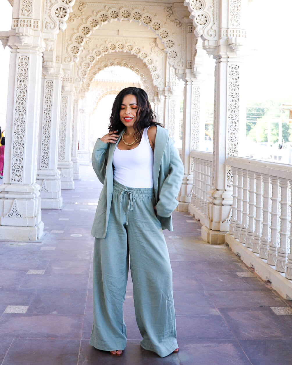 Petite women wearing a matching wide leg pants and blazer set outside in a temple
