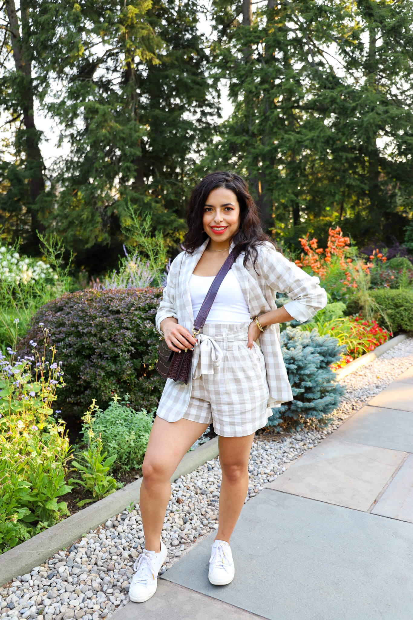 Woman wearing a matching plaid and shorts set in a garden